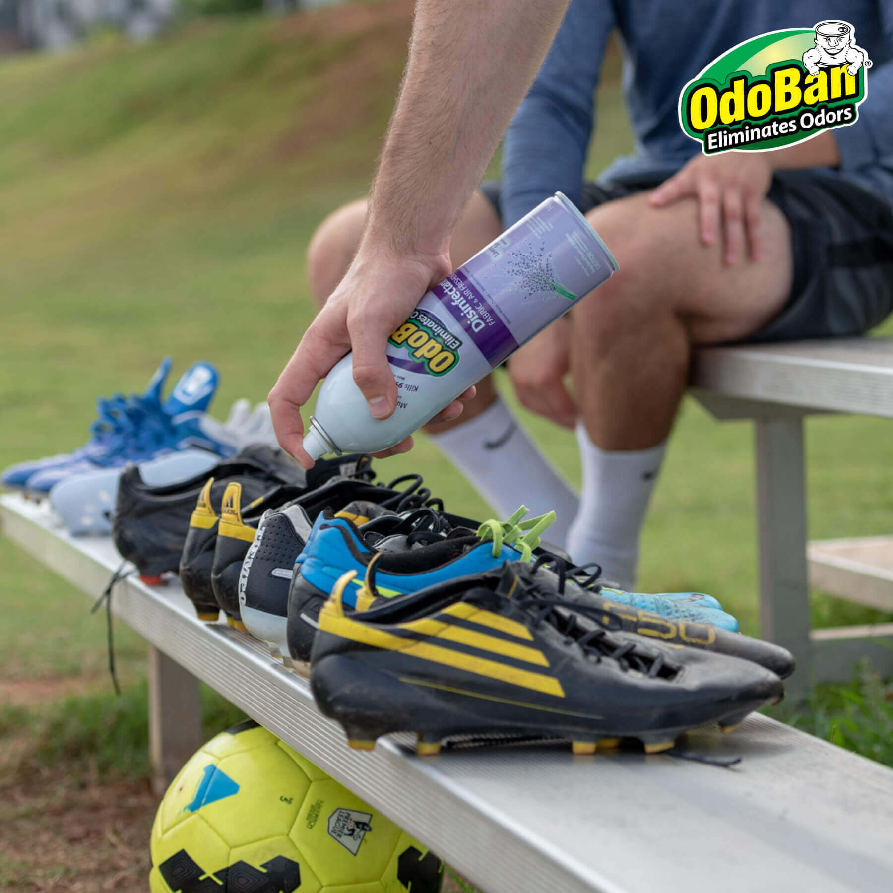 Man spraying OdoBan in smelly Soccer cleats.