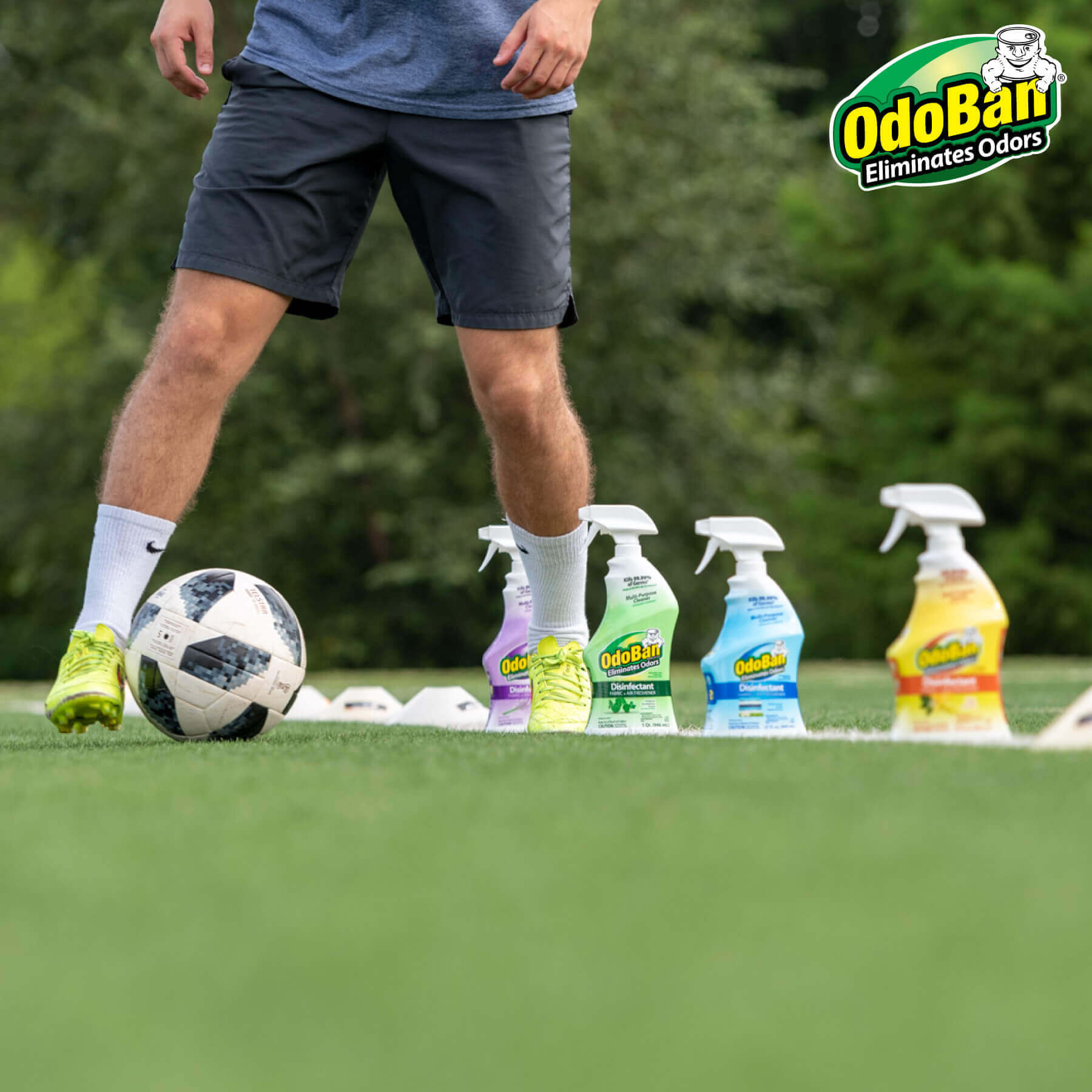 Man dribbling soccer ball between OdoBan products.